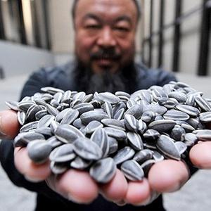 O artista chin�s Ai Weiwei com algumas das sementes de porcelana da obra Sunflower Seeds