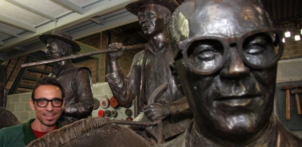 O artista Leo Santana posa ao lado de conjunto de esculturas que homenageia Guimarães Rosa - Divulgação