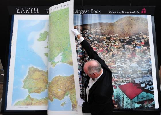 O editor australiano Gordon Cheers vira página de seu atlas, considerado o maior livro do mundo. O atlas tem 128 páginas e é vendido por US$  100 mil - AFP