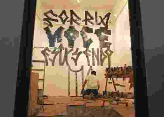 """Tony de Marco escreve a frase """"Sorria, você está sendo filmado"""" em parede da """"galeria"""", em São Paulo, no primeiro dos vinte dias de projeto (02/12/2010) - Willians Valente / UOL"""