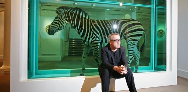 """O artista britânico Damien Hirst ao lado de sua obra """"The Incredible Journey"""", constituída por uma zebra conservada em formol (08/09/2008) - Getty Images"""