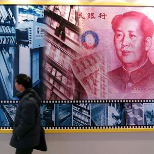Visitante passa diante do pôster que mostra o processo de desenho e impressão da moeda chinesa, o yuan, durante exposição sobre o conhecimento financeiro no Museu Nacional da China, em Pequim (09/12/2005) - Reuters/China News Photo