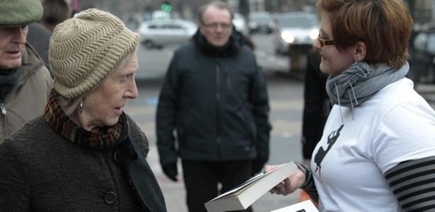 """Voluntária distribui livro na inauguração do evento """"World Book Night"""" - BBC"""