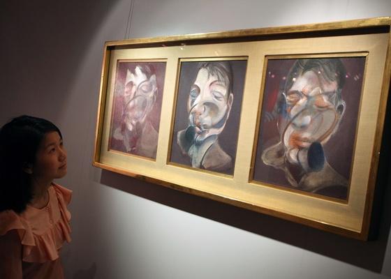 """Criança observa obra de Francis Bacon """"Three Studies for Self Portrait"""", a peça é estimada em 30 milhões de dólares (2/4/2011) - AFP PHOTO / ED JONES"""