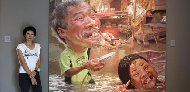 """A artista Lampu Kansanoh ao lado de seu quadro, intitulado """"As inundações são melhores que a seca"""", na galeria Ardel de Bangcoc, na Tailândia (15/06/2011) - EFE"""