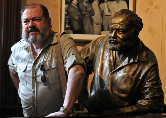 Um dos participantes do XIII Colóquio Internacional sobre Ernest Hemingway posa ao lado da estátua do escritor em no bar El Floridita em Havana, Cuba (16/6/2011) - EFE/Alejandro Ernesto