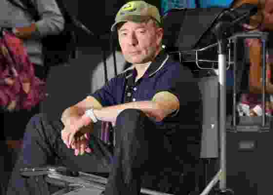 O escritor Tony Parsons posa sentado em bagagem no aeroporto de Heathrow, em Londres (3/8/2011) - AFP PHOTO / BEN STANSALL