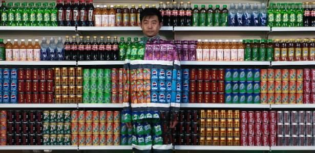 """O artista chinês Liu Bolin pinta em seu corpo rótulos de bebidas para ficar """"invisível"""" - AP"""
