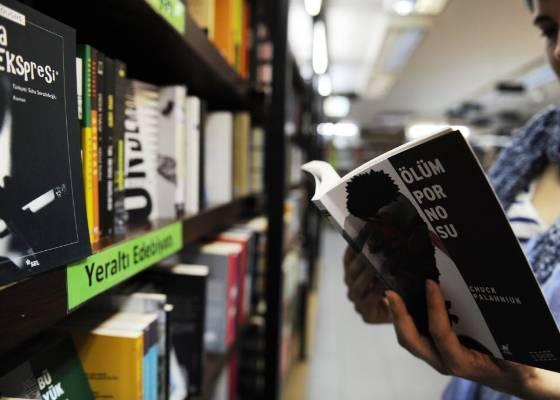 Mulher segura livro do autor americano Chuck Palahaniuk, um dos censurados pelo governo da Turquia - AFP PHOTO/BULENT KILIC