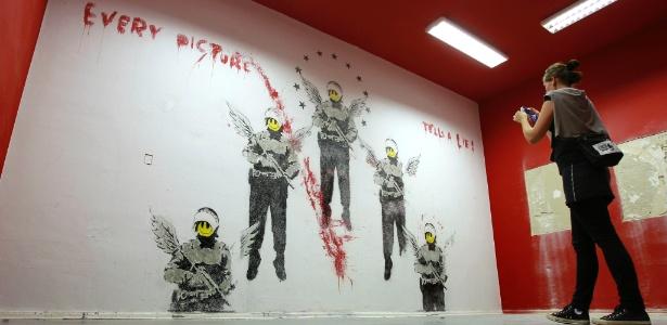 """Obra de Banksy ironiza imagem de soldados com asas de anjo e """"Smile"""" sob os dizeres """"Every Picture Tells a Lie"""" (Toda imagem diz uma mentira) - AP Photo/Michael Sohn"""