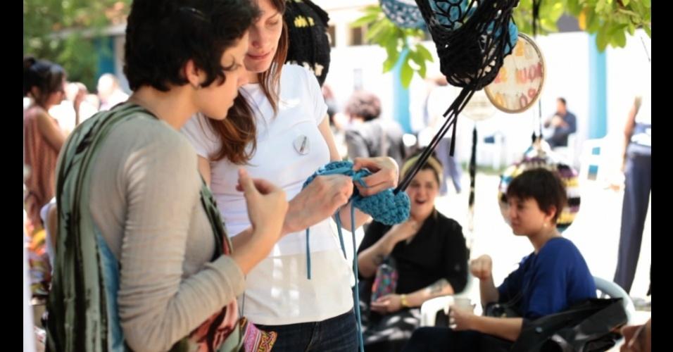 Cris Bertoluci, da Tresponto, mostra peça de tricô para uma das participantes de um dos piqueniques do coletivo, que usa os encontros ao ar livre para tricotar