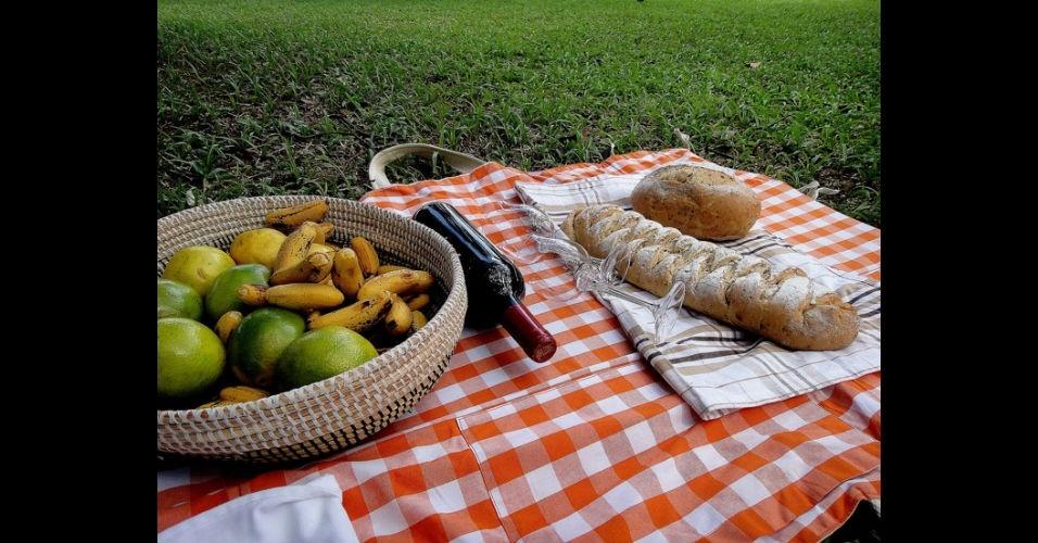 """Frutas, pães e vinho sobre toalha de um dos piqueniques do grupo de """"piqueniqueiros"""" Piperca, de São Paulo"""