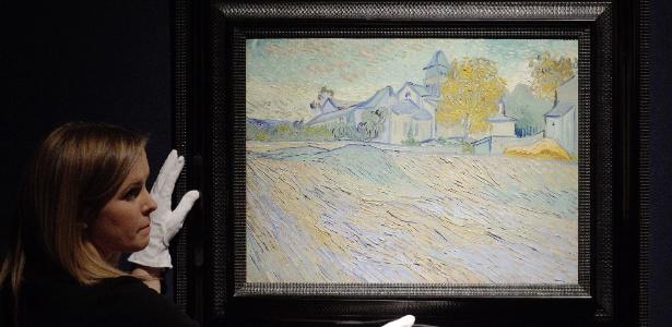 """Funcionária da casa de leilão Christie""""s exibe obra de Van Gogh, """"Vue de l""""asile et de la Chapelle de Saint-Remy"""", que pertencia à Elizabeth Taylor e que vai a leilão - EFE/Kerim Okten"""
