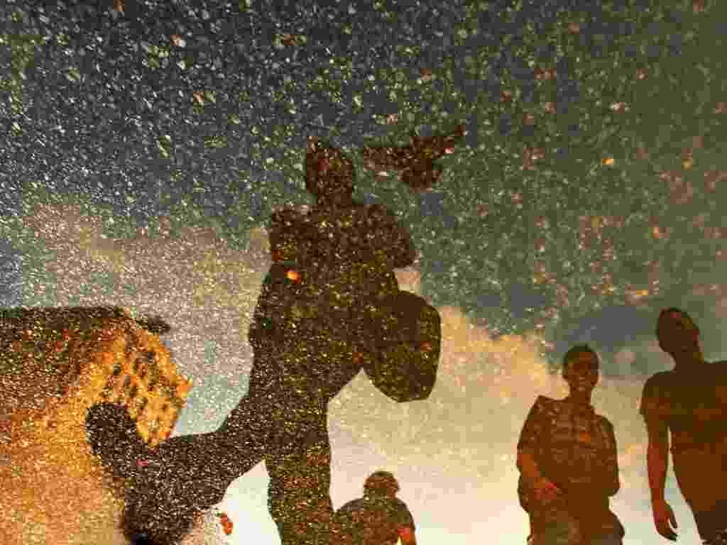As fotos, feitas na Union Square, em Manhattan, misturam o granulado escuro do piso da praça ao reflexo vibrante das cores na água (2012) - Ira Fox / Caters