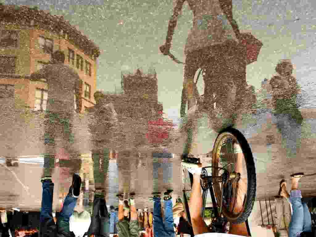 Para muitos um dia de chuva é algo a se lamentar, mas não para o fotógrafo novaiorquino Ira Fox, cujo trabalho depende justamente dos dias de chuva ? ele retrata os reflexos do cotidiano em poças d´água no chão (2012)  - Ira Fox / Caters